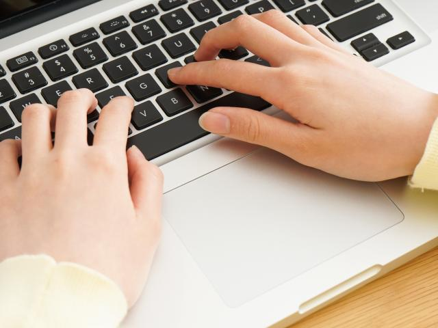 Young woman typing with laptop